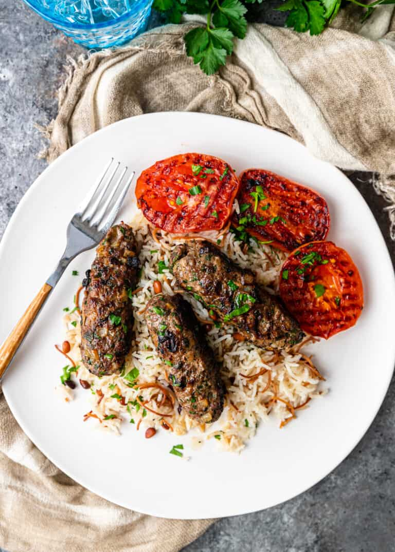 overhead image: beef kofta on white dinner plate with rice and grilled tomatoes