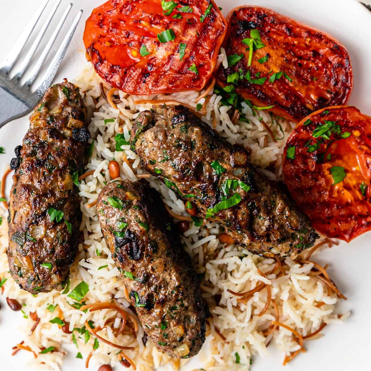 overhead image: kafta grilled ion bed of rice with side of grilled tomato slices