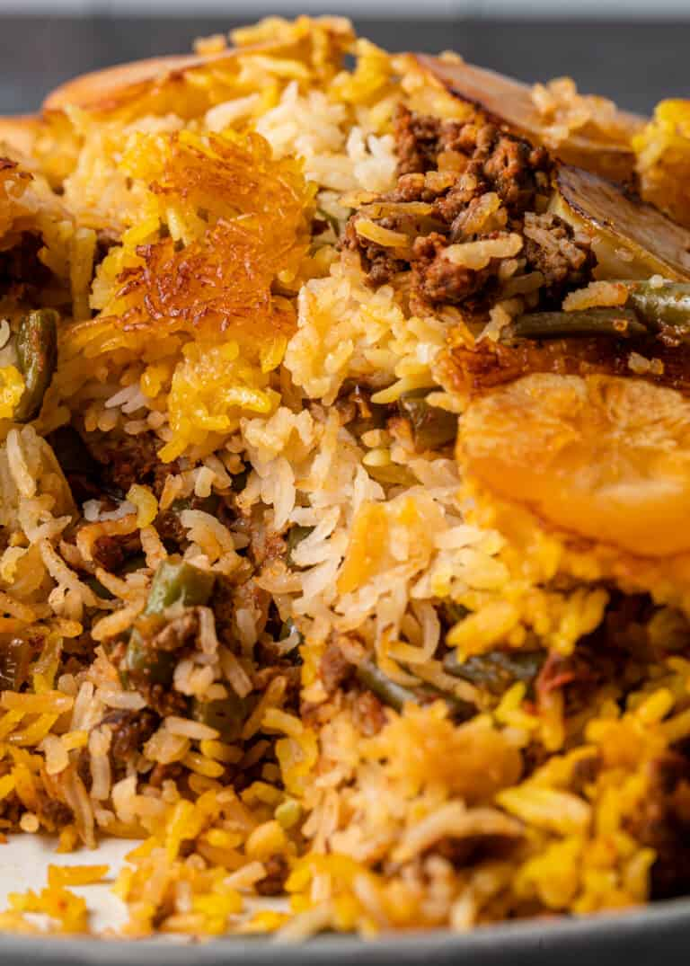 close up image of Persian casserole with rice, potatoes, green beans and ground meat
