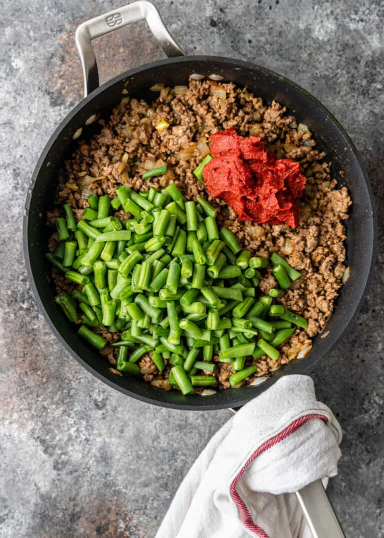 overhead image: ground lamb, green beans, and tomato paste in large skillet