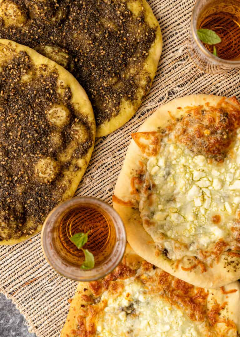 overhead image closeup: two pieces of zaatar bread and two pieces of cheese manakish