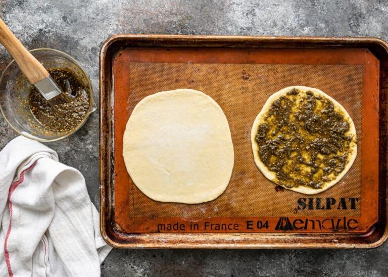 brushing olive oil and zaatar seasoning onto flatbread dough for zaatar manakish
