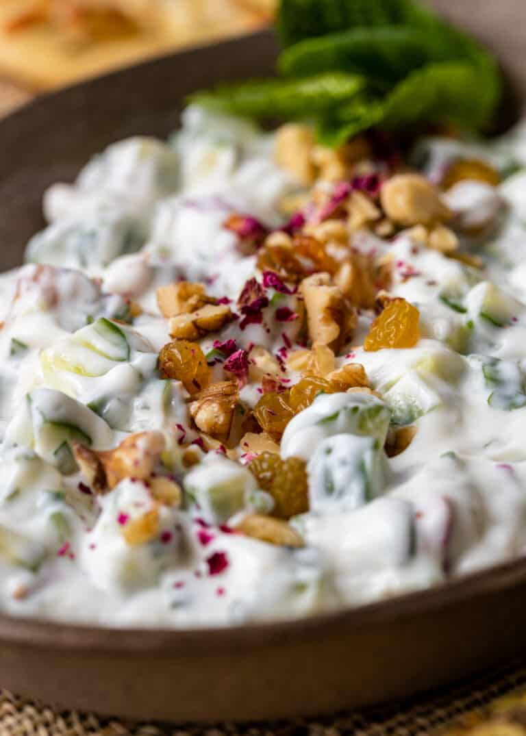 close up image of diced cucumbers in creamy yogurt sauce with walnuts
