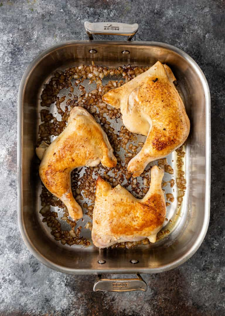overhead image: browned chicken thighs and legs in roasting pan