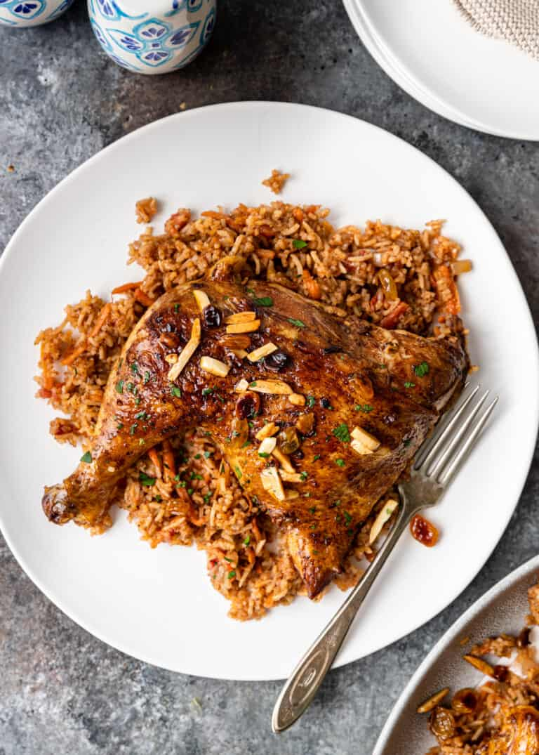overhead image: middle eastern chicken and rice on white plate with fork
