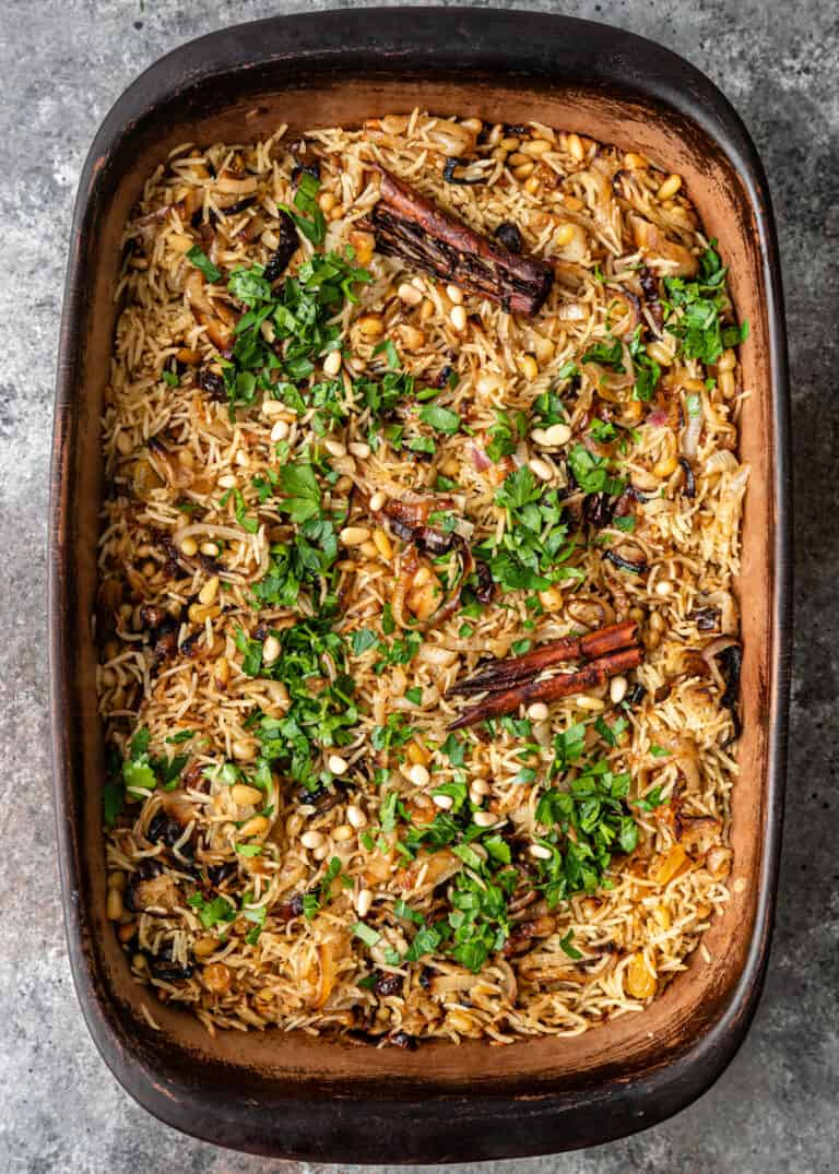 overhead photo: oven baked rice casserole with dried cherries, golden raisins, pine nuts and cinnamon sticks, with sprinkling of fresh parsley
