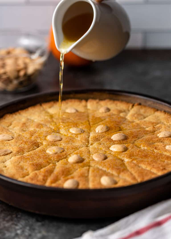 pouring orange water sugar glaze over top of baked Egyptian basbousa cake