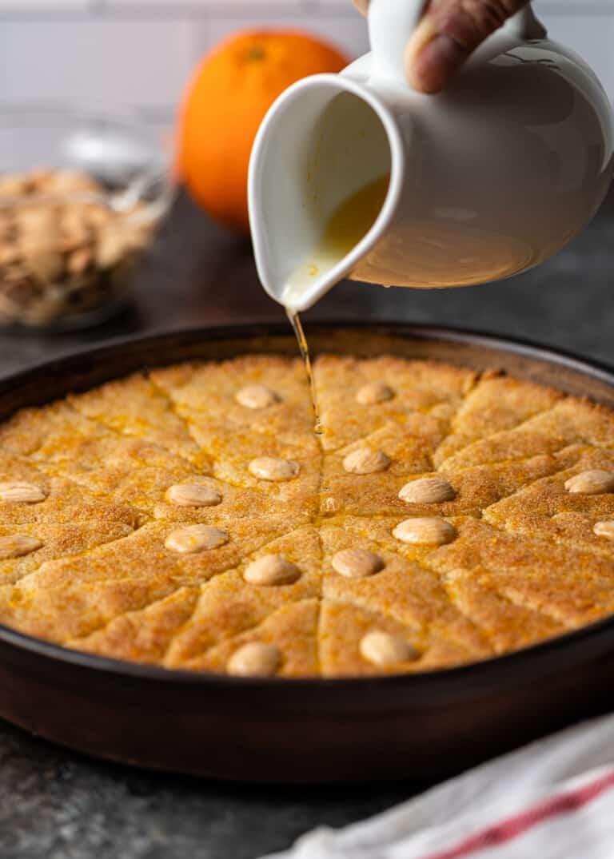 pouring orange sugar glaze over top of baked cake