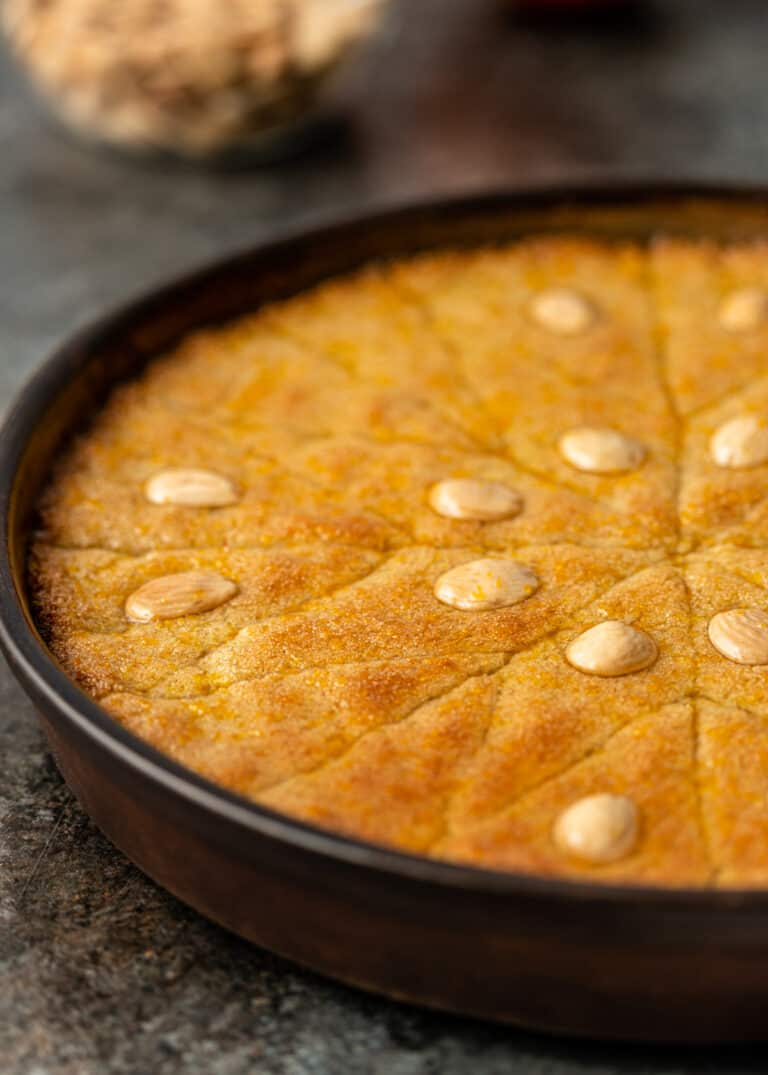 side view of basbousa cake topped with marcona almonds in round cake pan