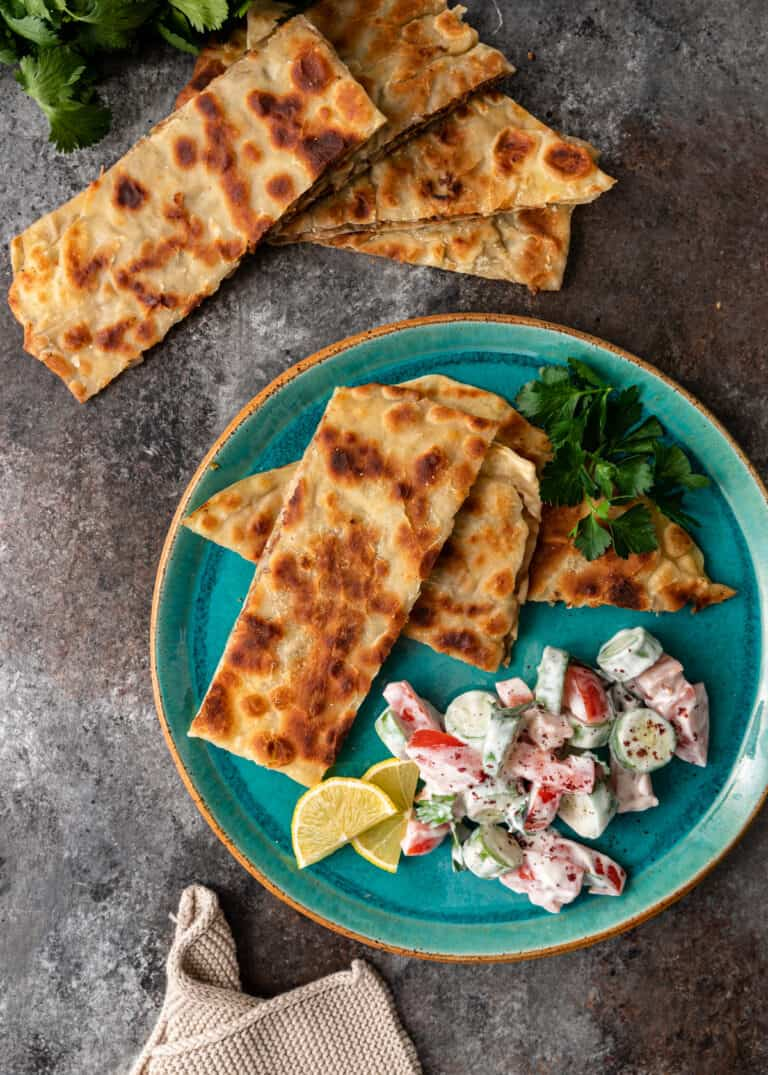 overhead: rectangular pieces of crispy flatbread on plate with creamy vegetable salad