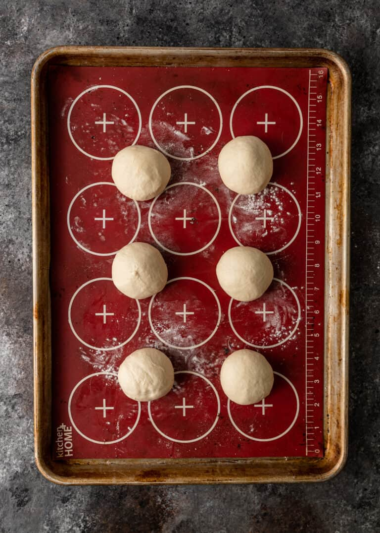overhead: balls of bread dough on lined baking sheet