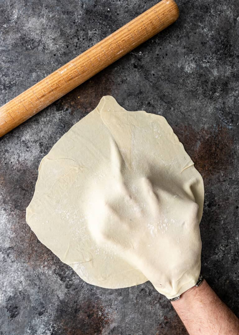 overhead: man's hand holding thin sheet of flatbread dough