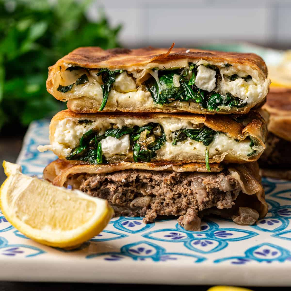 Three Gozleme (Turkish Stuffed Flatbread) stacked on decorative square plate