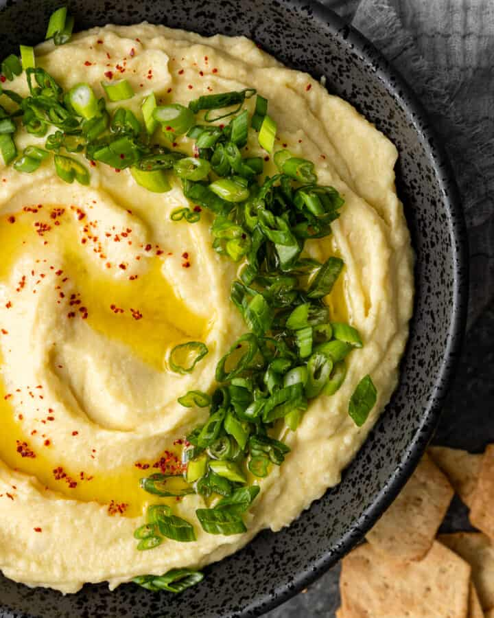 close up overhead image: bowl of Greek mashed potatoes garnished with scallions