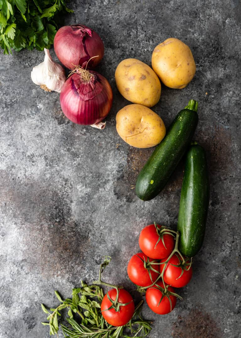 overhead photo: fresh vegetables arranged on counter top for briam recipe