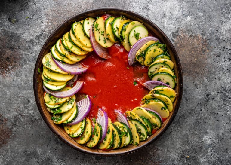 layering Greek vegetables into round pan for a briam