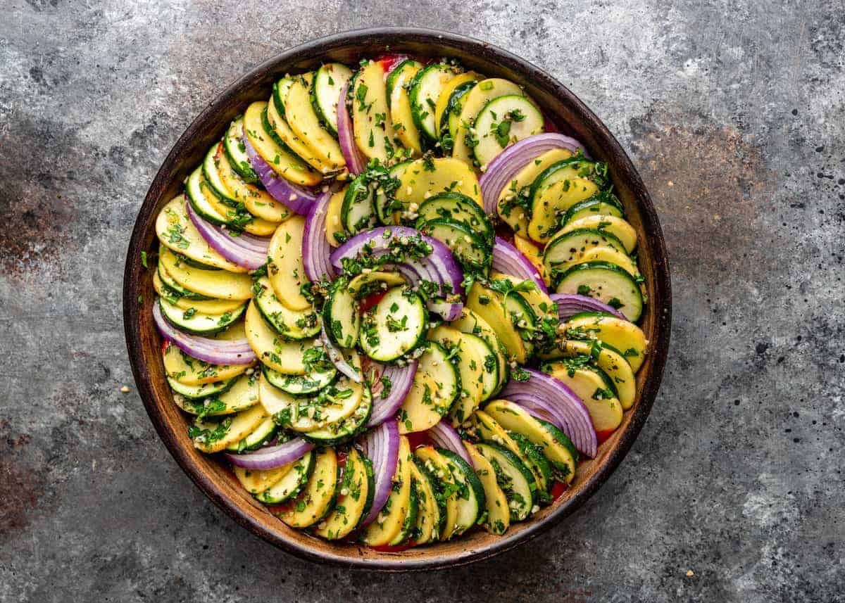 layer of red onion, yellow squash and zucchini slices in round casserole dish