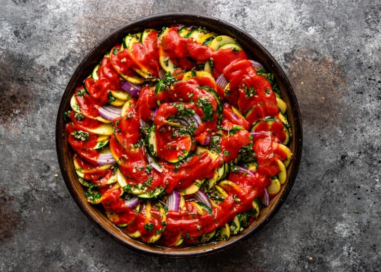 overhead image: unbaked Greek briam in round dish