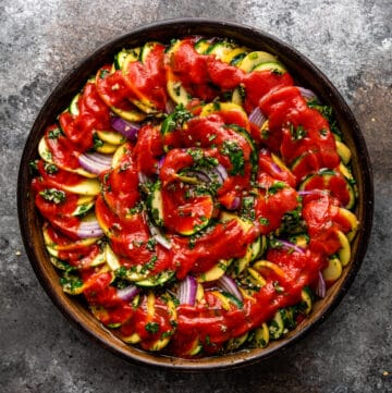 overhead image: Greek roasted vegetables on round platter topped with tomato sauce