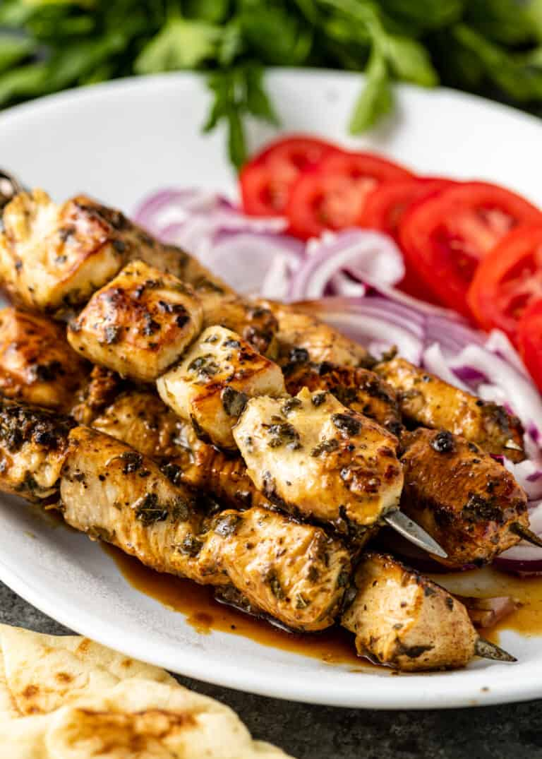 platter of Greek chicken kabobs next to red onion and tomato
