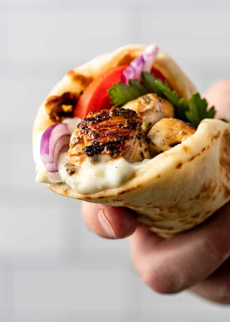 man's hand holding Greek street food (grilled chicken and vegetables wrapped in a pita)