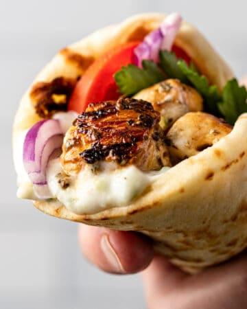 closeup: man's hand holding a pita wrapped around grilled chicken souvlaki