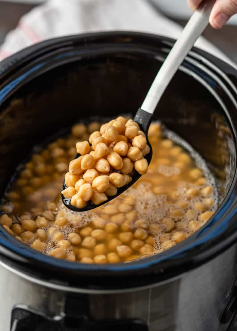 garbanzo beans on serving spoon above slow cooker