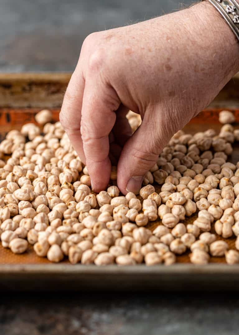 man's hand sorting dried garbanzo beans