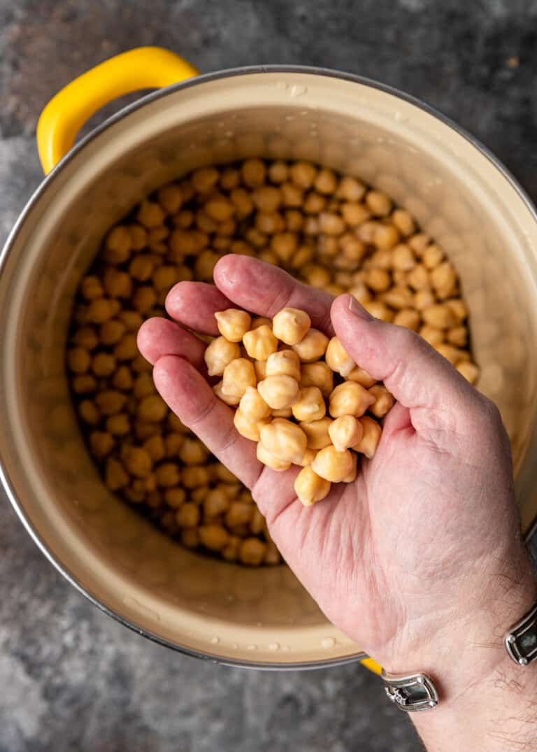 man holding handful of cooked chickpeas above a yellow pot