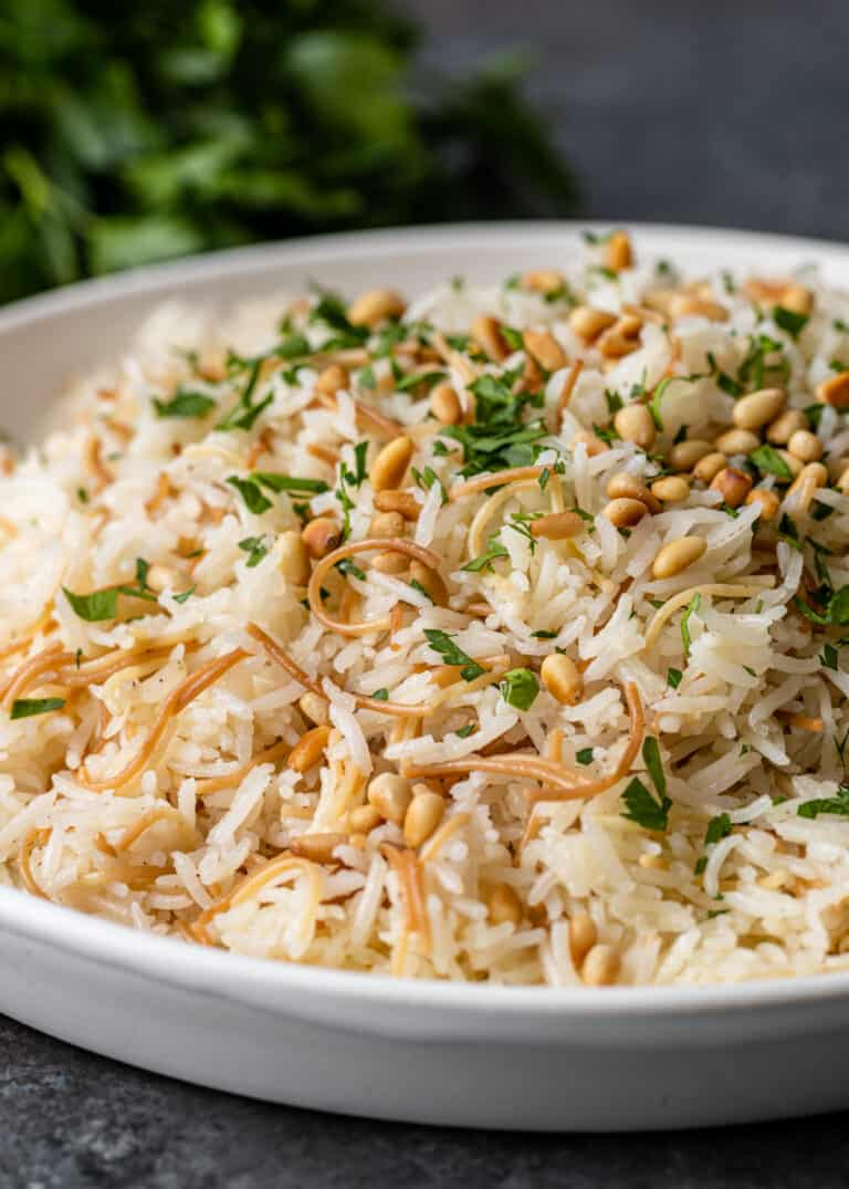dish of lebanese rice pilaf garnished with pine nuts and parsley