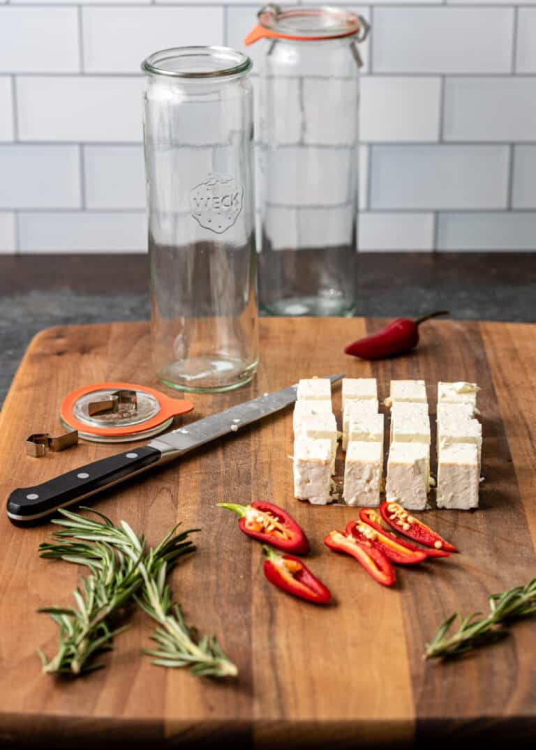 large wooden cutting board with cubes of fresh feta, rosemary sprigs, birdseye chili peppers and supplies for marinating cheese