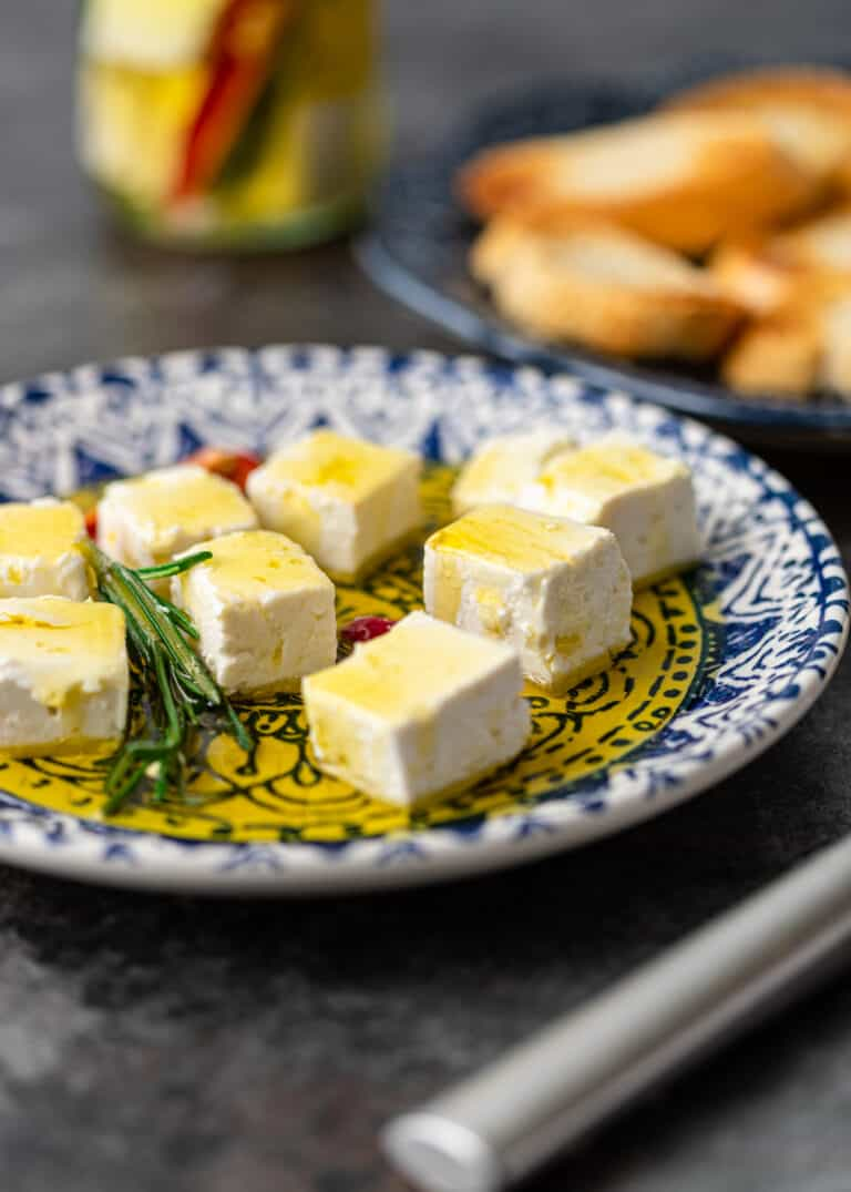 white marinated cheese cubes on small appetizer plate