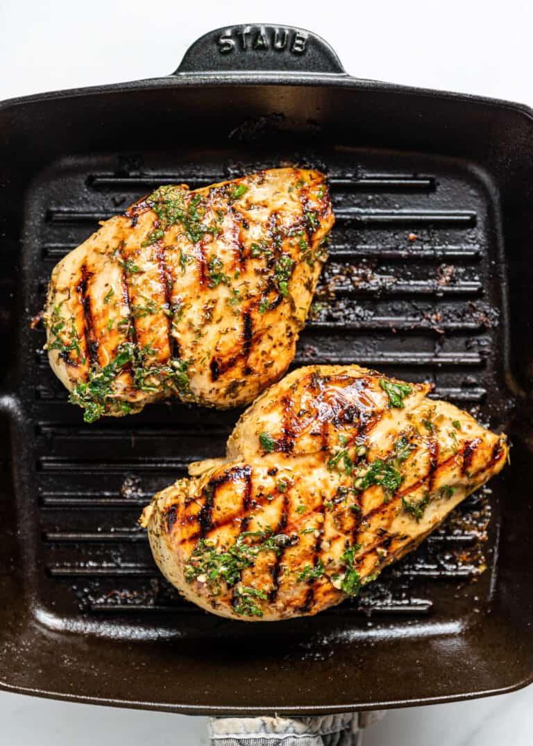 overhead: 2 chicken breasts on a grill pan covered in Mediterranean chicken marinade