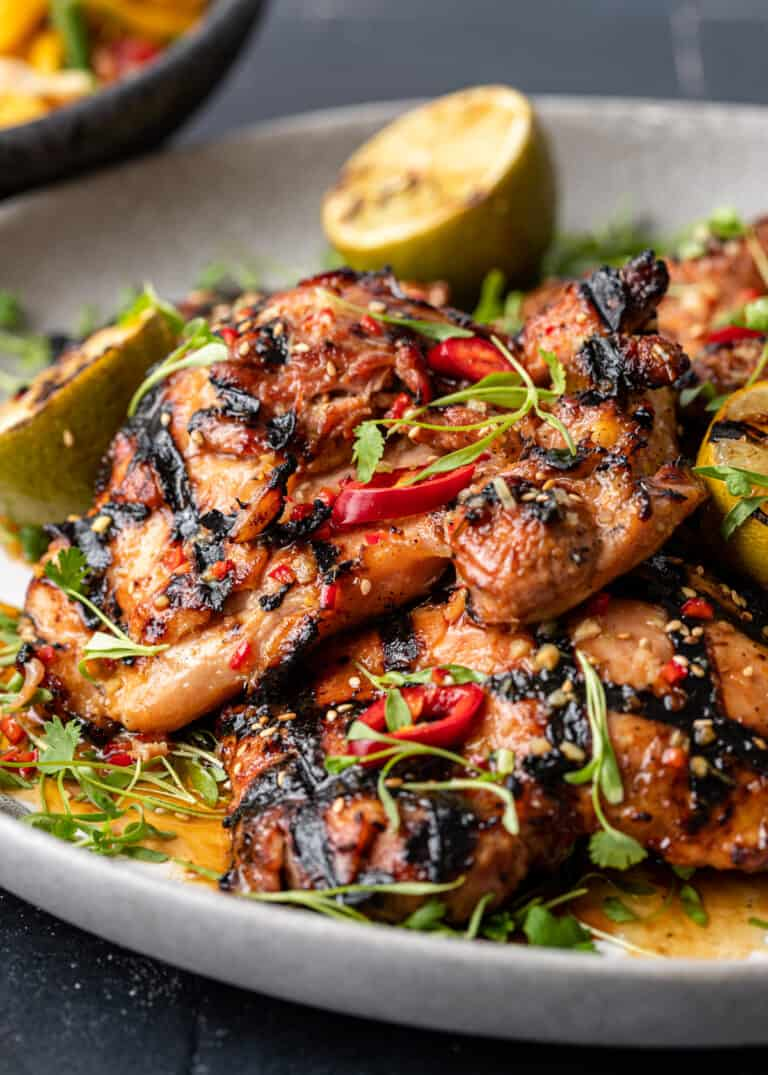 grilled chicken thighs on round serving platter garnished with red chili peppers and lemongrass