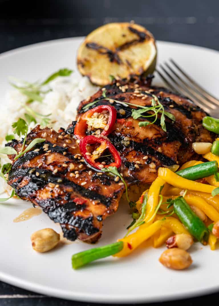 Thai grilled chicken thighs on dinner plate with stir fried vegetables