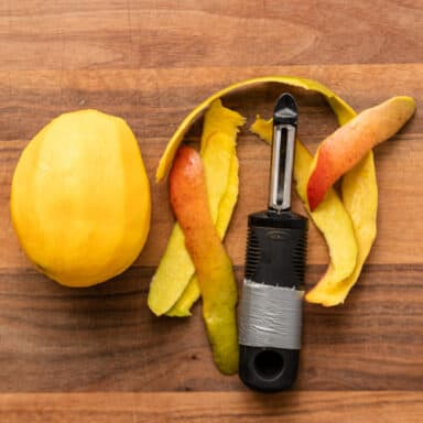 peeled mango and vegetable peeler on wooden cutting board