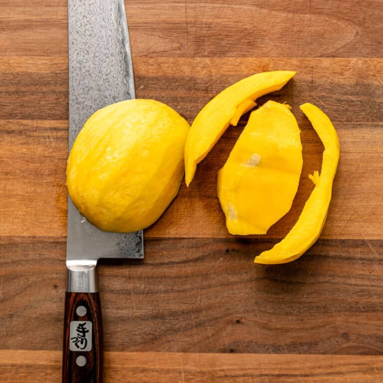 overhead: mango cut away from the pit on wooden cutting board with chef's knife