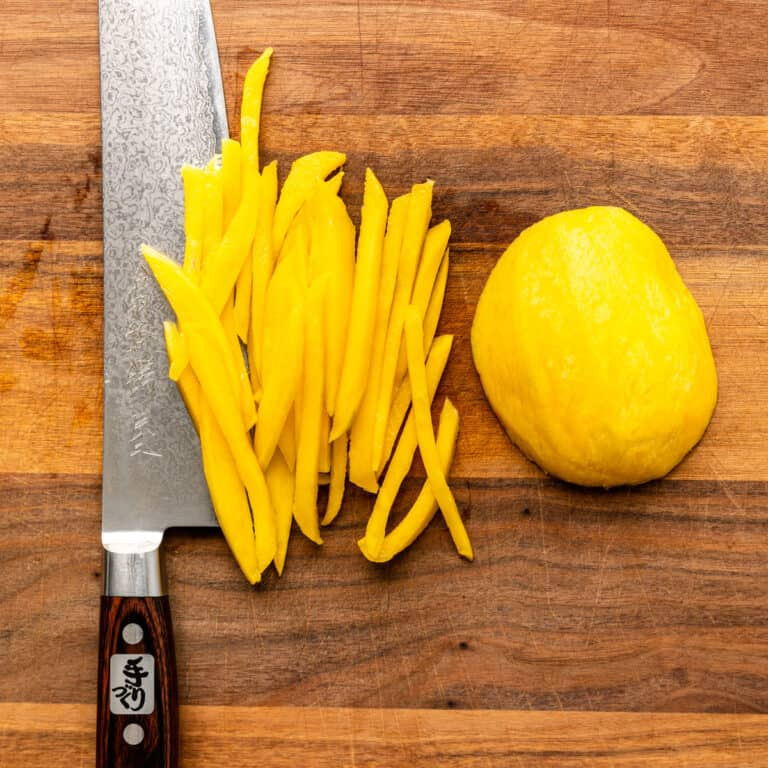 overhead: julienne strips of green mango and a large Chef's knife on cutting board