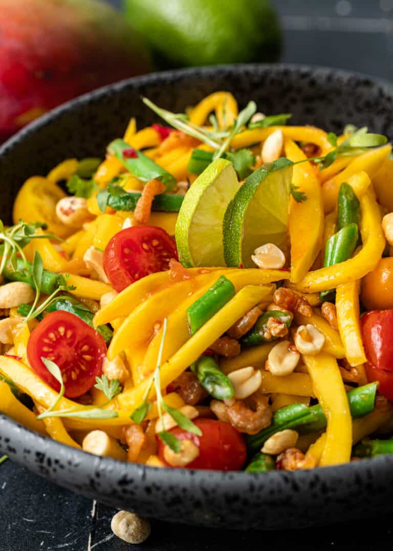 side view close up: green mango salad with mango fruit, tomatoes, beans, and peanuts in black bowl