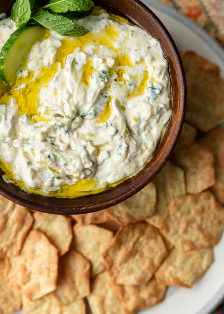 overhead: crackers scattered around bowl of creamy yogurt sauce with cucumbers, mint, and drizzle of olive oil