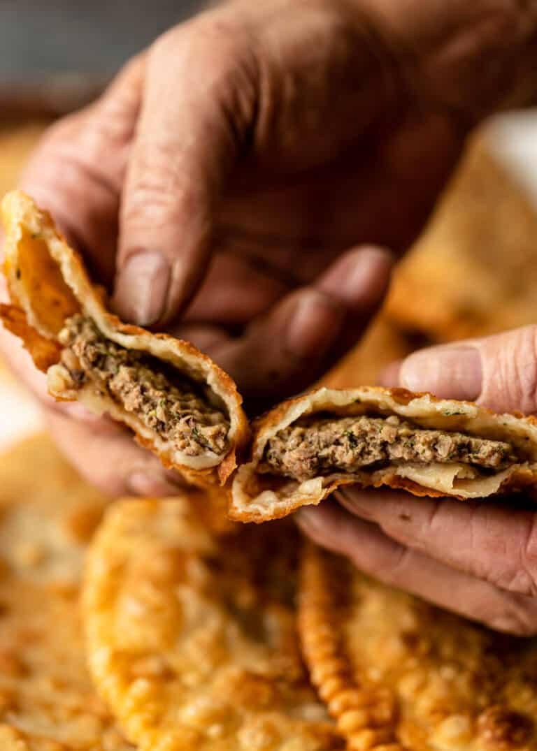 man's hands holding pieces of Russian chebureki, revealing the meat filling inside