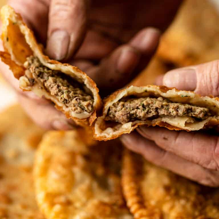 close up of man's hands holding savory fried turnovers (cut open to reveal the meat filling)