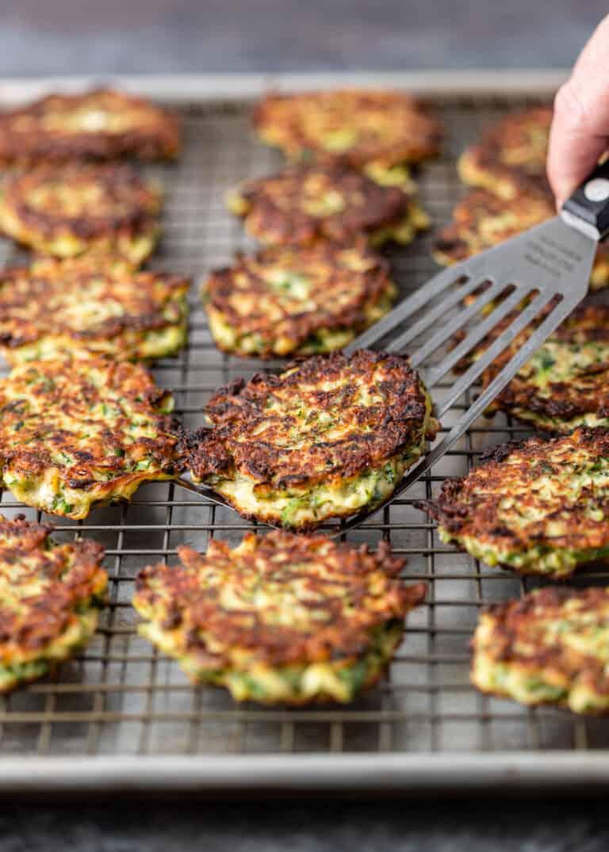 sliding metal spatula under golden brown crispy pan fried zucchini fritters on metal baking rack