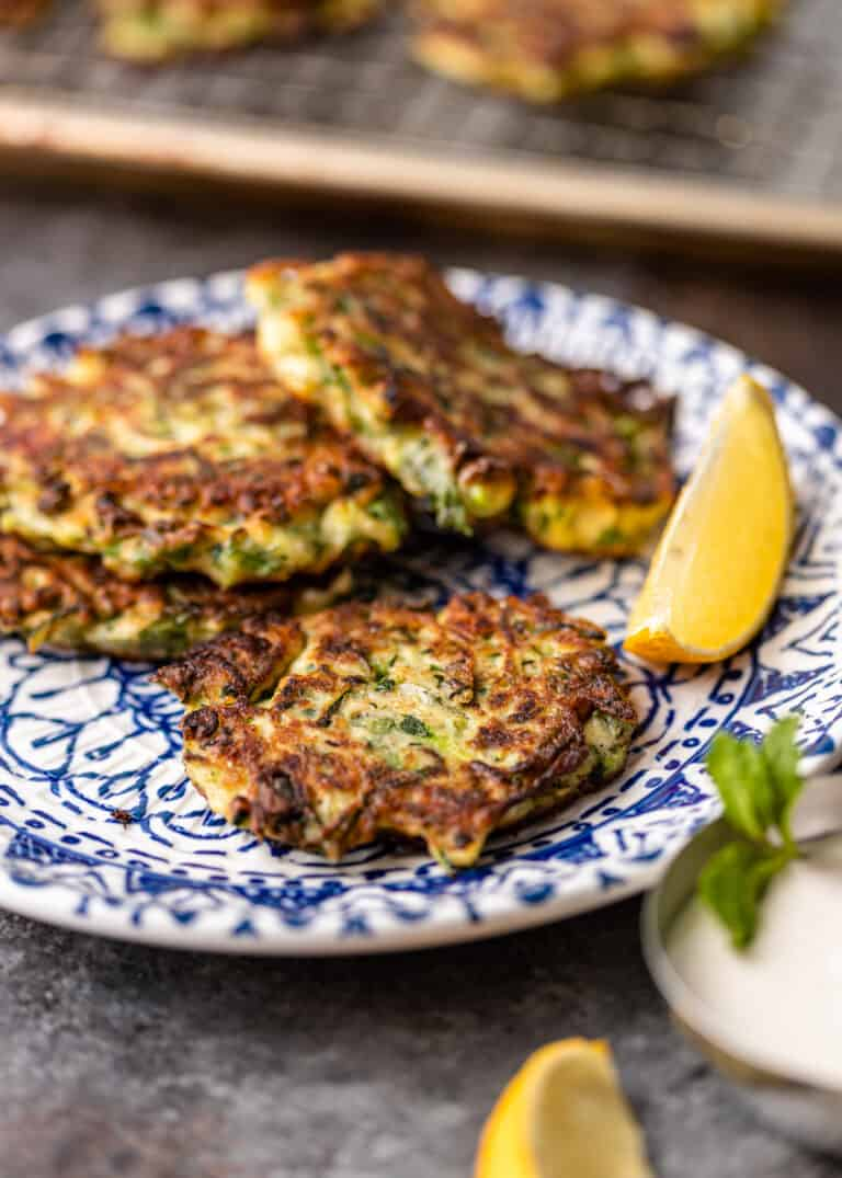 4 Greek zucchini pancakes on small blue and white plate with lemon wedge