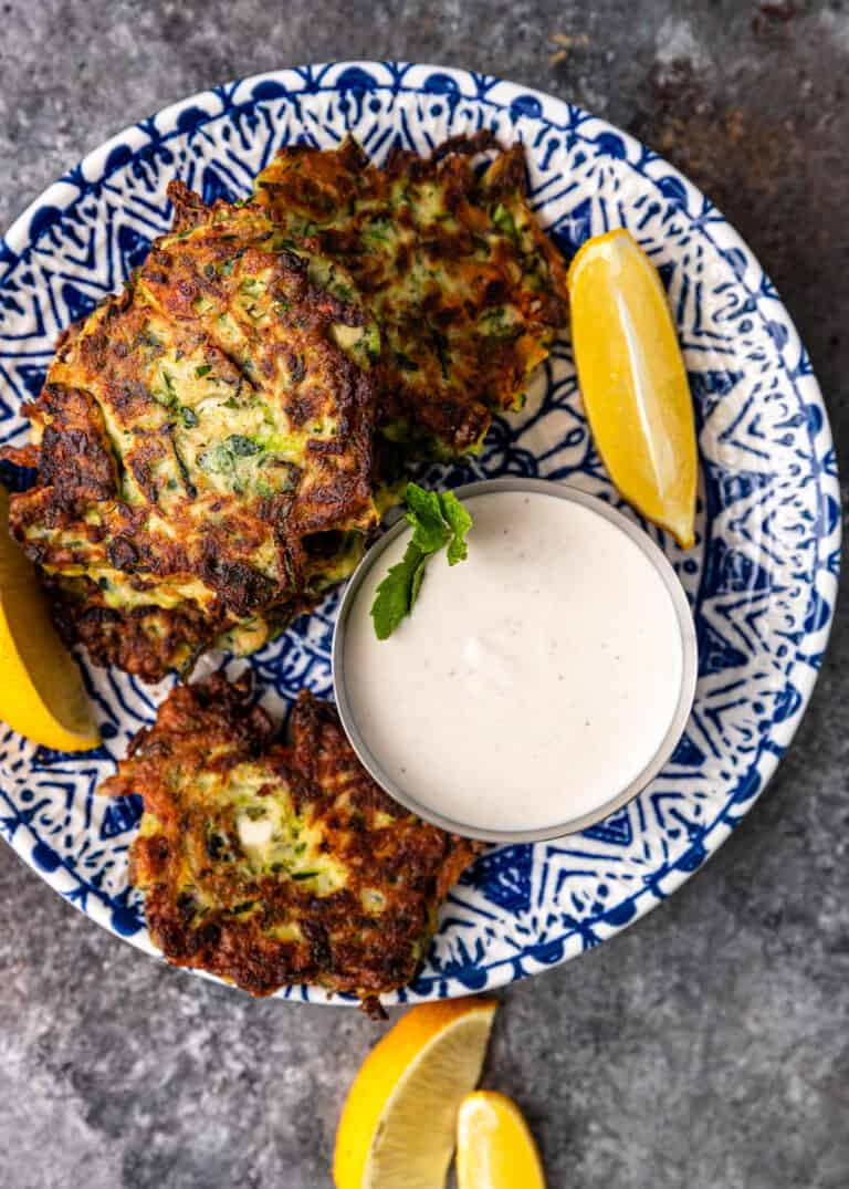 overhead image: crispy fried shredded zucchini patties on blue and white plate with cup of mint yogurt sauce