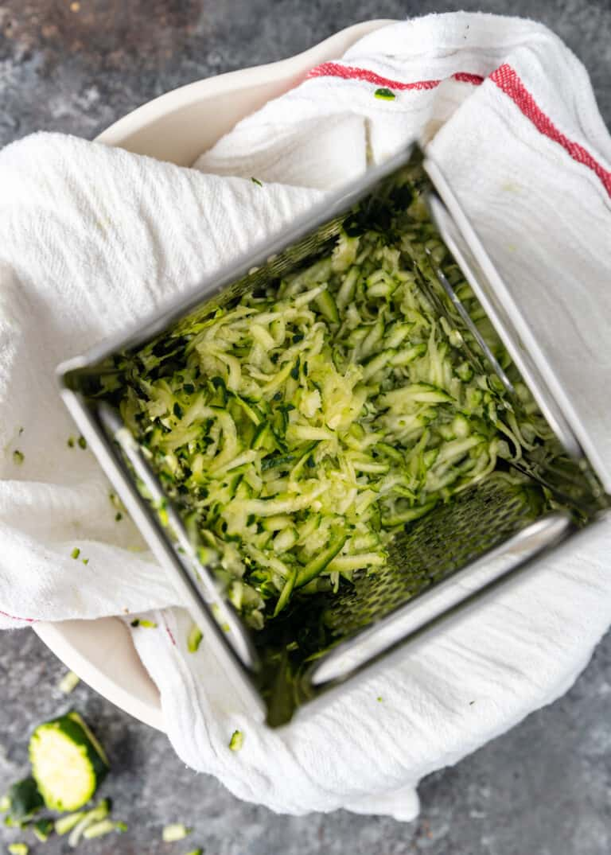 grating zucchini onto white kitchen towel for Greek fritters (Kolokithokeftedes)