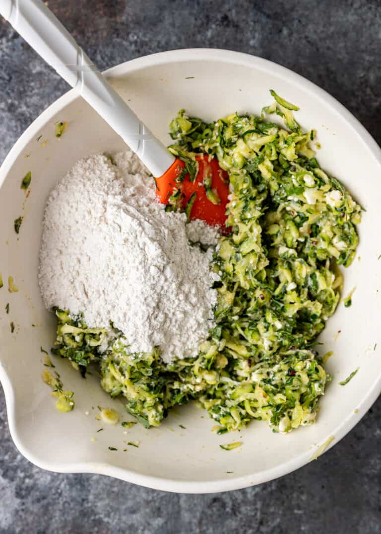 mixing ingredients in bowl to make batter for Greek zucchini fritters