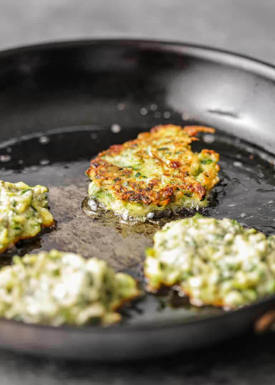 crispy fried squash patties cooking in pan of oil