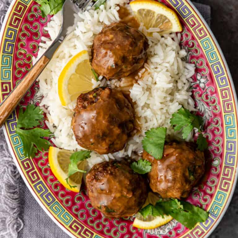 overhead image: plate of Asian lemon cilantro chicken meatballs served over white rice with lemon slices