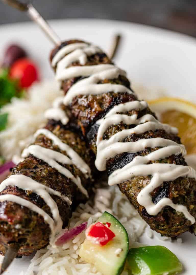 two ground beef skewers drizzled with yogurt sauce